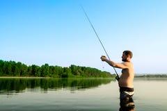 Pesca del pescador en un río tranquilo por la mañana Hombre en las artes de pesca stending en un río y tiros trole Fotografía de archivo libre de regalías