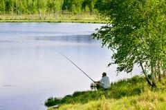 Pesca del pescador por el lago Fotos de archivo libres de regalías