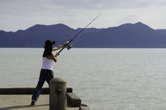 Pesca del pescador que pesca con cebo de cuchara en el mar Imagenes de archivo