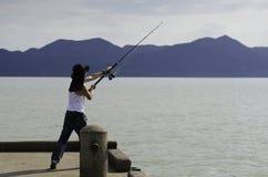 Pesca del pescatore che pesca a traina nel mare Immagini Stock