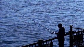 Pesca del pescatore con la filatura, siluetta stock footage