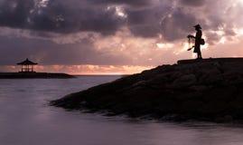 Pesca del pescatore di balinese su una spiaggia ad alba Immagine Stock Libera da Diritti