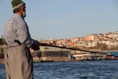 Pesca del pescatore nella città Immagini Stock