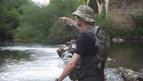 Pesca del pescatore sul fiume, tenente canna da pesca stock footage