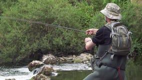 Pesca del pescatore sul fiume, tenente canna da pesca archivi video