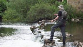 Pesca del pescatore sul fiume, tenente canna da pesca video d archivio