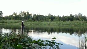 Pesca del pescatore in un fiume calmo di mattina Uomo in attrezzatura per la pesca che stending in un fiume archivi video