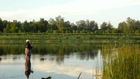 Pesca del pescatore in un fiume calmo di mattina Uomo in attrezzatura per la pesca che stending in un fiume e nei tiri una canna  archivi video
