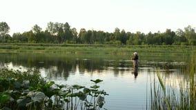 Pesca del pescatore in un fiume calmo di mattina Uomo in attrezzatura per la pesca che stending in un fiume e nei tiri una canna  stock footage