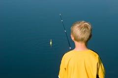 Pesca del ragazzo con il Bobber Fotografia Stock Libera da Diritti