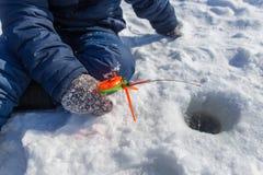 Pesca del ragazzo con una canna da pesca sul ghiaccio nell'inverno fotografie stock