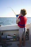 Pesca del ragazzo da una barca. Immagini Stock
