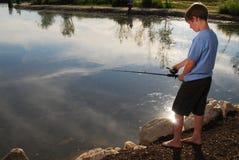 Pesca del ragazzo in un lago fotografie stock libere da diritti