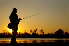 Pesca del señuelo pesca del pescador en la puesta del sol imagen de archivo
