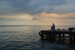 Pesca del viejo hombre en el muelle imagen de archivo