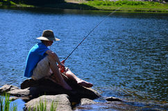 Pesca dell'adolescente su un lago Fotografie Stock