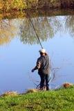 Pesca dell'anziano sul lago Immagine Stock