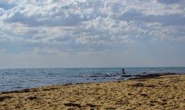 Pesca dell'uomo in acqua blu il giorno nuvoloso fotografia stock libera da diritti