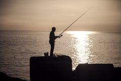 Pesca dell'uomo alla mattina Immagini Stock