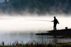 Pesca dell'uomo alla riva del fiume Fotografie Stock Libere da Diritti