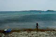 pesca dell'uomo alla spiaggia della riva di mare accanto ad un piccolo battello pneumatico davanti ad un ancoraggio immagini stock