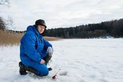 Pesca dell'uomo anziano sul lago al giorno di inverno freddo Fotografia Stock Libera da Diritti