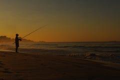 Pesca dell'uomo della siluetta sulla spiaggia Immagini Stock