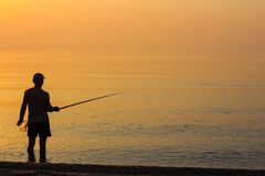Pesca dell'uomo nel mare ad alba Fotografia Stock Libera da Diritti