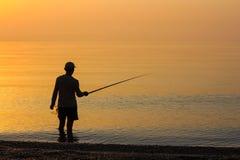 Pesca dell'uomo nel mare ad alba Immagine Stock Libera da Diritti