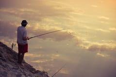 Pesca dell'uomo nella riflessione del cielo Immagini Stock