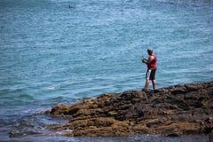 Pesca dell'uomo nelle pietre del mare Immagini Stock Libere da Diritti
