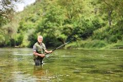 Pesca dell'uomo senior in un fiume un giorno soleggiato Fotografie Stock Libere da Diritti
