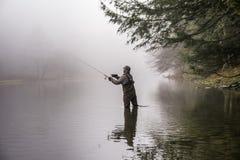 Pesca dell'uomo in un fiume Fotografie Stock Libere da Diritti