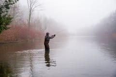 Pesca dell'uomo in un fiume Fotografia Stock Libera da Diritti