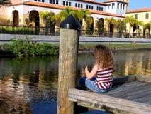 Pesca della bambina fuori dal bacino Fotografia Stock