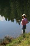 Pesca della donna nel lago Immagine Stock