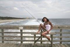 Pesca della donna sul pilastro fotografia stock