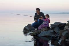 Pesca della figlia e del padre sul lago al tramonto Fotografie Stock