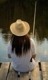 Pesca della giovane donna nello stagno di estate Fotografia Stock Libera da Diritti