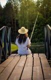 Pesca della giovane donna nello stagno di estate Immagini Stock Libere da Diritti