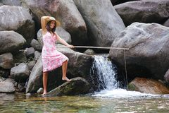 Pesca della ragazza del paese in un fiume della montagna Fotografie Stock