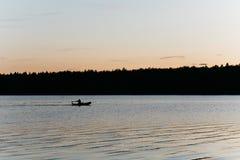 Pesca della siluetta su un piccolo lago immagine stock libera da diritti
