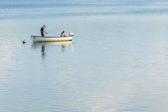 Pesca della trota in una piccola barca Immagine Stock