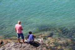 Pesca delle coppie nelle pietre del mare Fotografia Stock Libera da Diritti