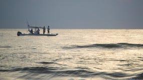 Pesca deportiva de los hombres apenas de la costa de la Florida en la salida del sol Fotografía de archivo libre de regalías
