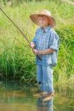 Pesca descalza del muchacho del pescador que se coloca en la charca de agua dulce transparente Foto de archivo libre de regalías