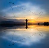 Pesca di lancio alla siluetta di tramonto Immagini Stock Libere da Diritti