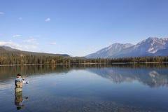 Pesca di mosca in montagne rocciose, Alberta, Canada fotografia stock