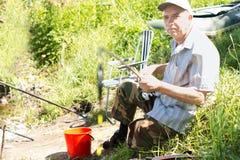 Pesca di seduta dell'uomo disabile anziano in un lago Immagine Stock