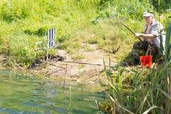 Pesca di seduta dell'uomo senior al bordo di un lago fotografia stock libera da diritti